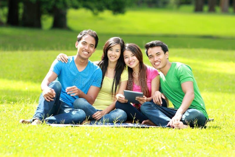 Gruppe des jungen Studenten, der den Tabletten-PC im Freien verwendet lizenzfreie stockfotografie