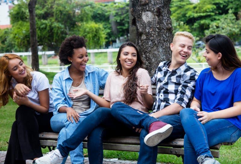 Gruppe des Kühlens von multi ethnischen jungen erwachsenen Leuten stockbilder