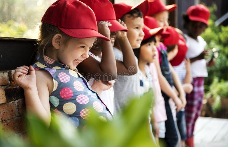 Gruppe des Kindergartens scherzt das Lernen draußen im Garten arbeiten Exkursionen lizenzfreie stockfotos