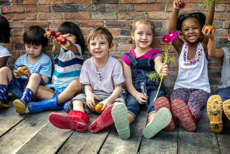 Gruppe des Kindergartens scherzt die kleinen Landwirte, welche die Gartenarbeit lernen stockfotografie