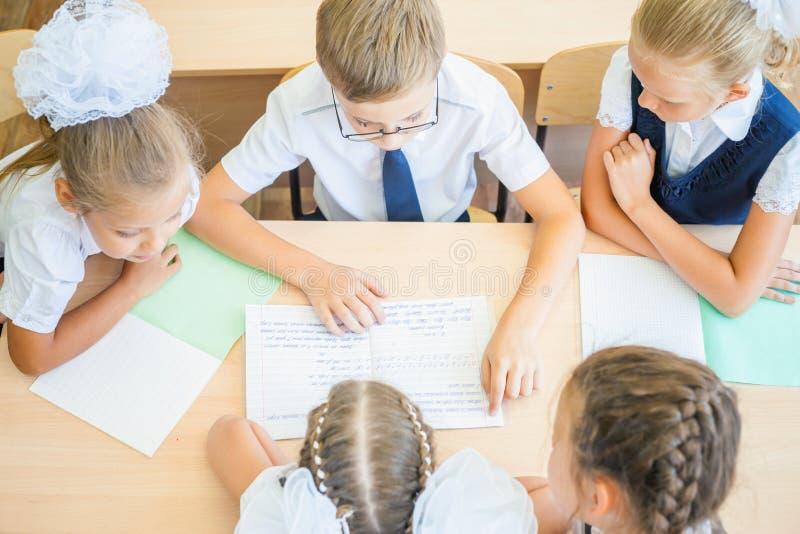Gruppe des Klassenzimmers der Schulkinder in der Schule, das am Schreibtisch sitzt stockbilder
