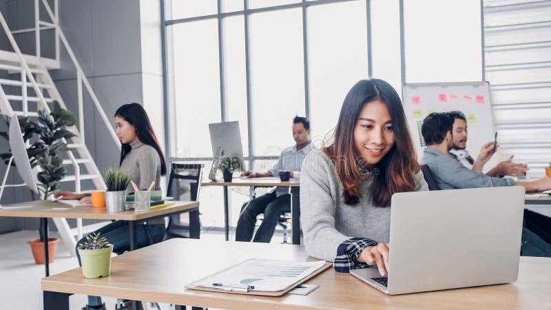 Gruppe des kreativen Designers der Verschiedenartigkeit, der am modernen Bürogebäude arbeitet zufälliger Bürolebensstil mit Techn stockfotos