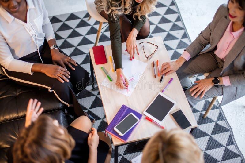 Gruppe des multiethnischen weiblichen Teams, das im Büro arbeitet stockfotografie