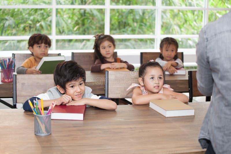 Gruppe des netten glücklichen kleines Kinderstudenten, der auf Tabelle mit Buch in der Volksschule des Klassenzimmers sich lehnt  stockbilder