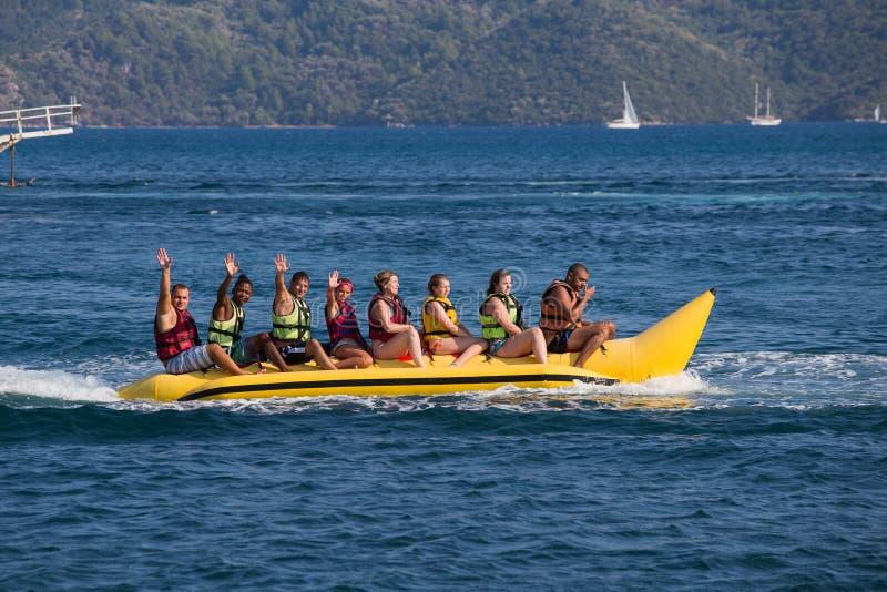 Gruppe des Reitenbananenbootes der jungen Leute stockfoto