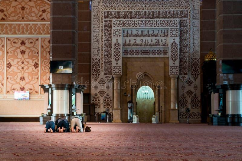 Gruppe des religiösen moslemischen Mannes, der innerhalb der Moschee betet islamisch stockbild
