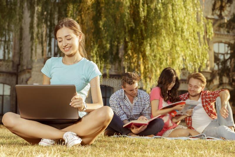 Gruppe des schönen jungen Studenten, der auf dem Gras sitzt stockbilder