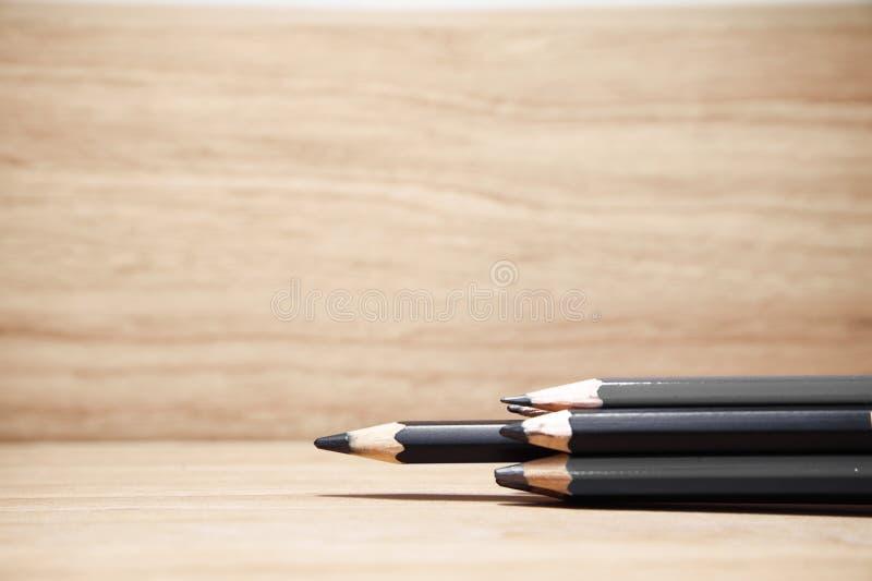 Gruppe des schwarze Farbscharfen Bleistifts auf hölzernem Hintergrund einer von heraus stockfoto