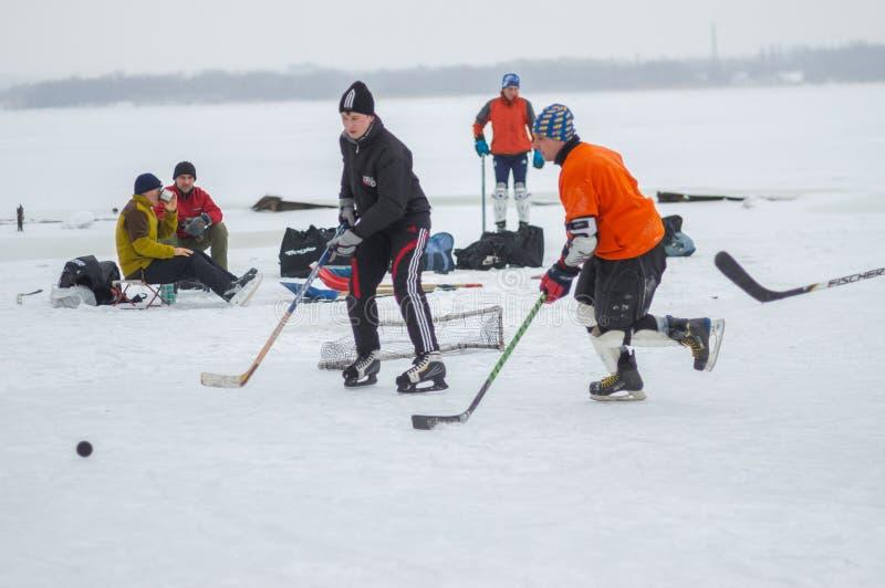 Gruppe des unterschiedlichen gealterten Leutespielens hokey und des Stillstehens auf einem gefrorenen Fluss Dnipro in Ukraine lizenzfreie stockbilder
