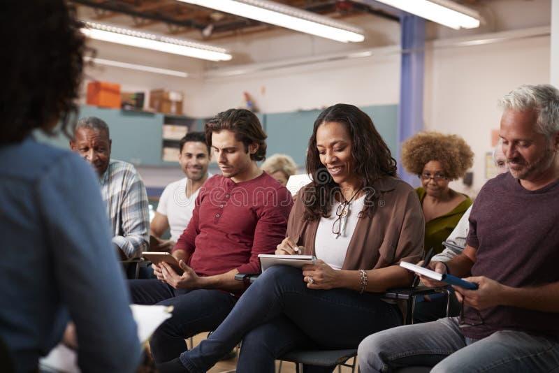 Gruppe, die Anmerkungen macht, während, an Nachbarschafts-Sitzung im Einkaufszentrum teilnehmend lizenzfreie stockfotografie