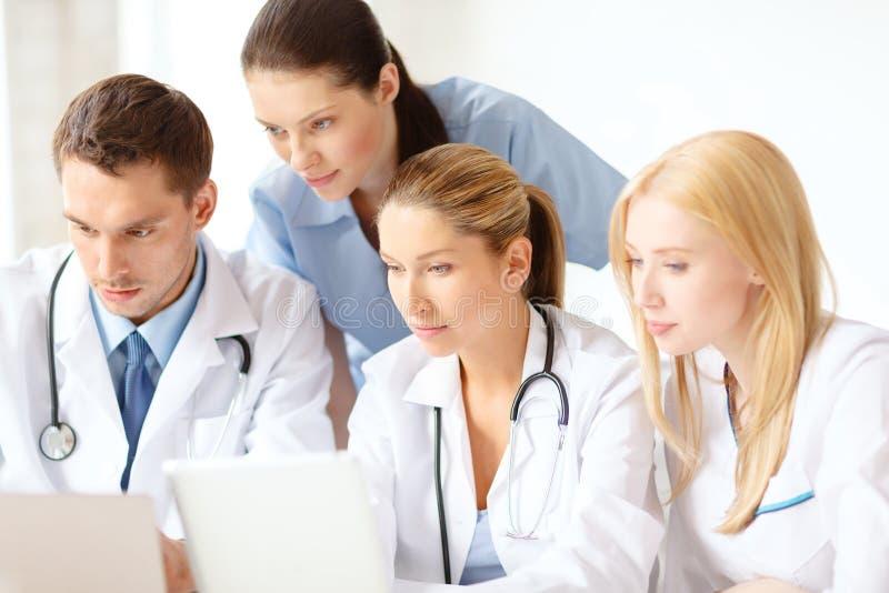 Gruppe Doktoren mit Laptop- und Tabletten-PC lizenzfreie stockbilder