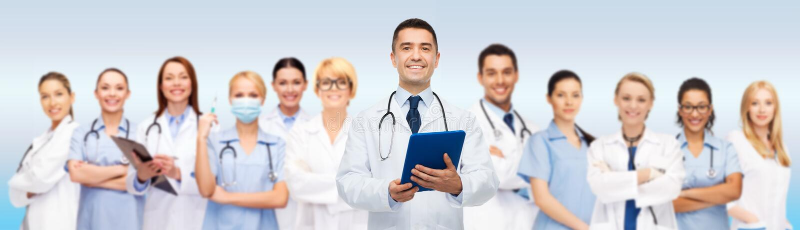 Gruppe Doktoren mit Tabletten-PC und -klemmbrett stockbild