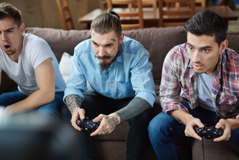 Gruppe emotionale Freunde, die Videospiele spielen lizenzfreie stockbilder