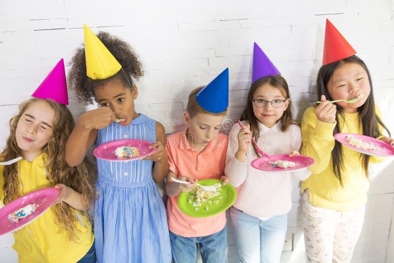 Gruppe entzückende Kinder, die Spaß an der Geburtstagsfeier haben, essen Kuchen stockbild