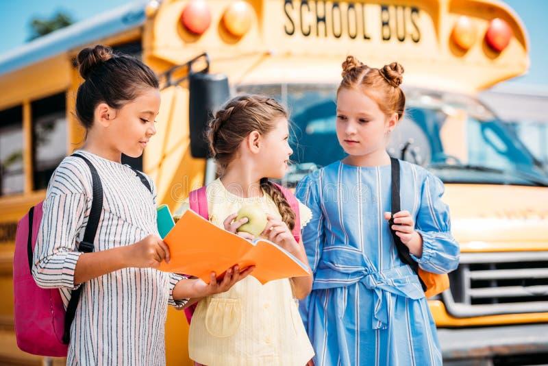 Gruppe entzückende kleine Schulmädchen mit Notizbuch sprechend vor lizenzfreie stockbilder