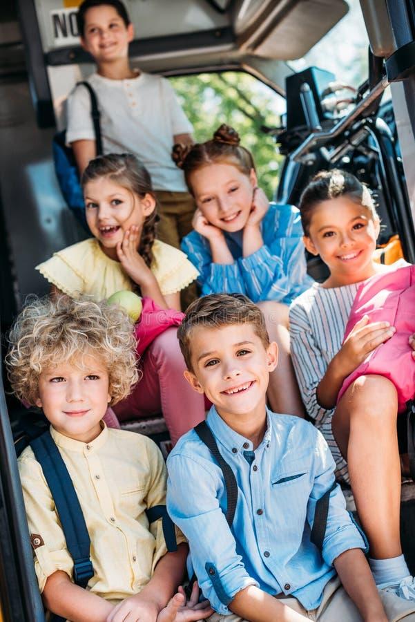 Gruppe entzückende Schüler, die auf Treppe des Schulbusses und des Schauens sitzen lizenzfreie stockfotos