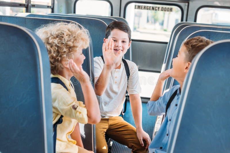 Gruppe entzückende Schüler, die zusammen hohe fünf beim Reiten geben lizenzfreies stockfoto