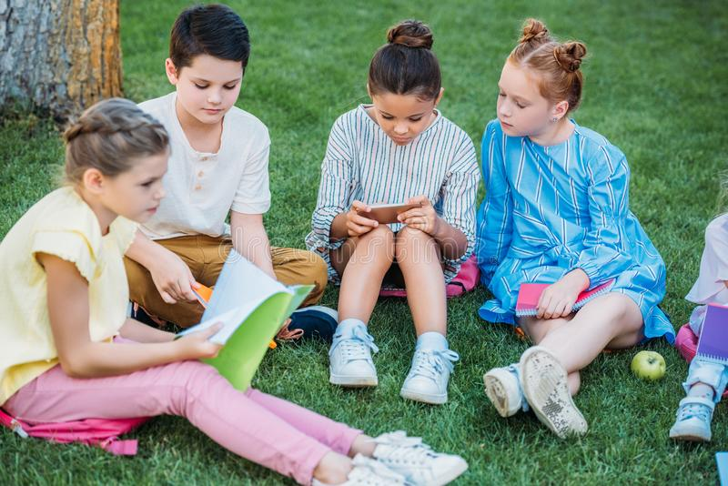 Gruppe entzückende Schüler, die zusammen Zeit auf Gras verbringen lizenzfreies stockbild