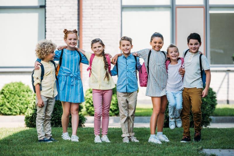 Gruppe entzückende Schulkinder, die in der Schule Garten und das Schauen stehen lizenzfreies stockfoto