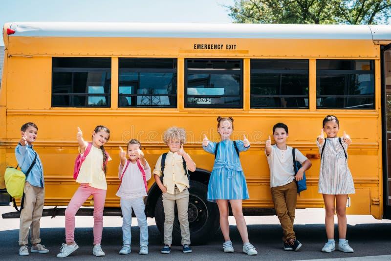 Gruppe entzückende Schulkinder, die vor Schulbus und dem Darstellen stehen lizenzfreies stockfoto