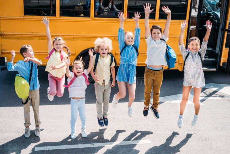 Gruppe entzückende Schulkinder, die vor Schulbus und dem Schauen springen stockbild