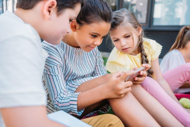 Gruppe entzückende Schulkinder, die zusammen Smartphone beim Sitzen verwenden lizenzfreies stockfoto