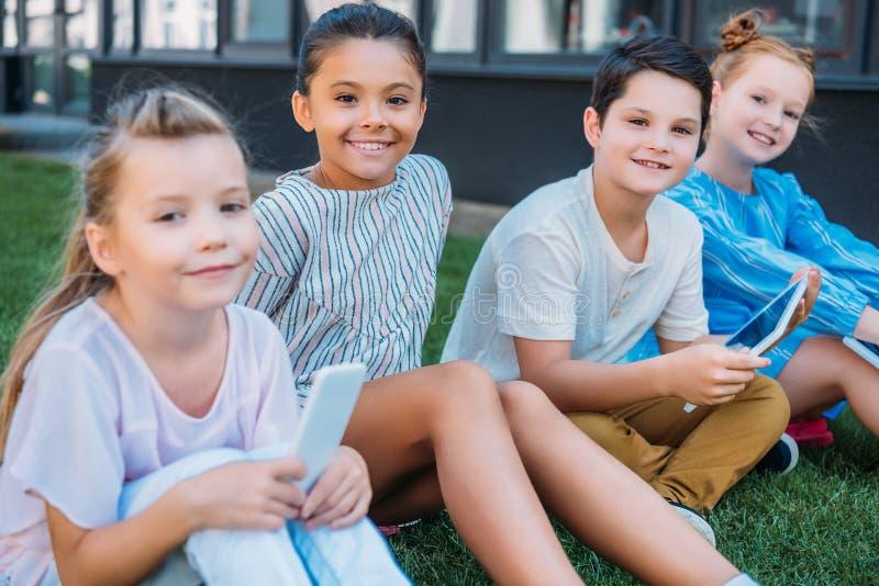Gruppe entzückende Schulkinder mit den dugutal Geräten, die auf Gras und dem Schauen sitzen stockfotos