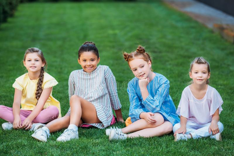 Gruppe entzückende Schulmädchen, die zusammen auf grünem Gras und dem Schauen sitzen lizenzfreie stockfotos
