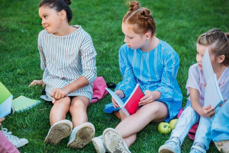 Gruppe entzückende Schulmädchen, die zusammen Zeit auf Gras verbringen stockbilder