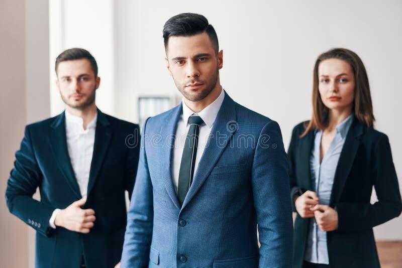Gruppe erfolgreiche Geschäftsleute mit ihrem Führer in der Front lizenzfreie stockfotos