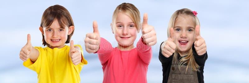 Gruppe Erfolgsdaumen der Kinderkinderlächelnde junge kleinen Mädchen herauf Positiv stockbild