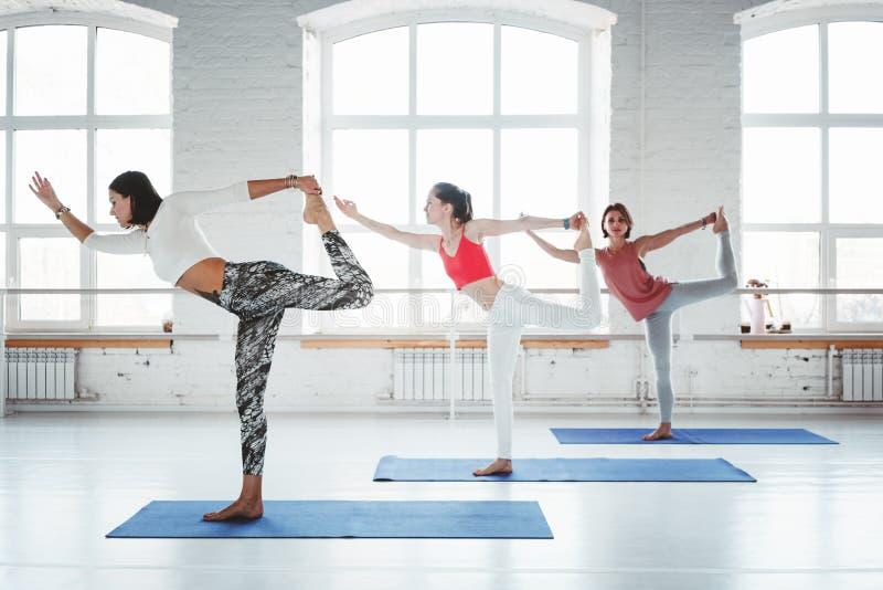 Gruppe erwachsenes gesundes Frauenpraxisyoga wirft zusammen frühen Morgen der Innenklasse auf Gesundes Lebensstilkonzept lizenzfreie stockfotos
