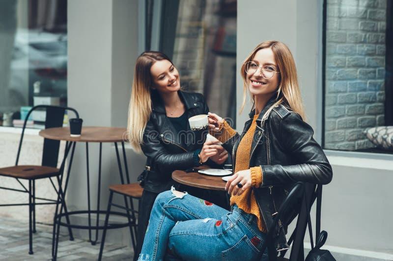 Gruppe europäische Mädchen, die einen Kaffee zusammen trinken Zwei Frauen am Café sprechend, lachend, klatschend und ihre Zeit ge lizenzfreie stockfotografie