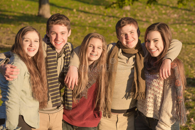 Gruppe fünf Teenager-Umfassung stockfoto