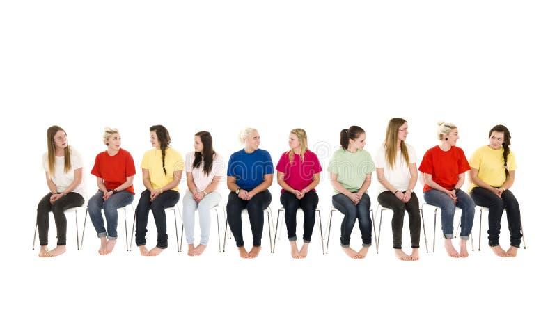 Gruppe Frauen auf Stühlen in einer Zeile lizenzfreie stockbilder