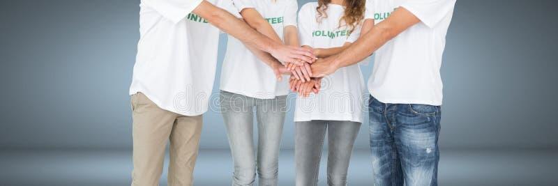 Gruppe freiwillige stehende und Verbindungshände der Leute zusammen mit Vignettenhintergrund stockfotografie