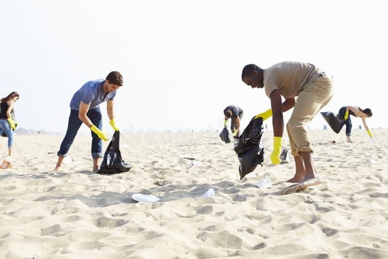 Gruppe Freiwilligen, die Abfall auf Strand aufräumen stockbilder