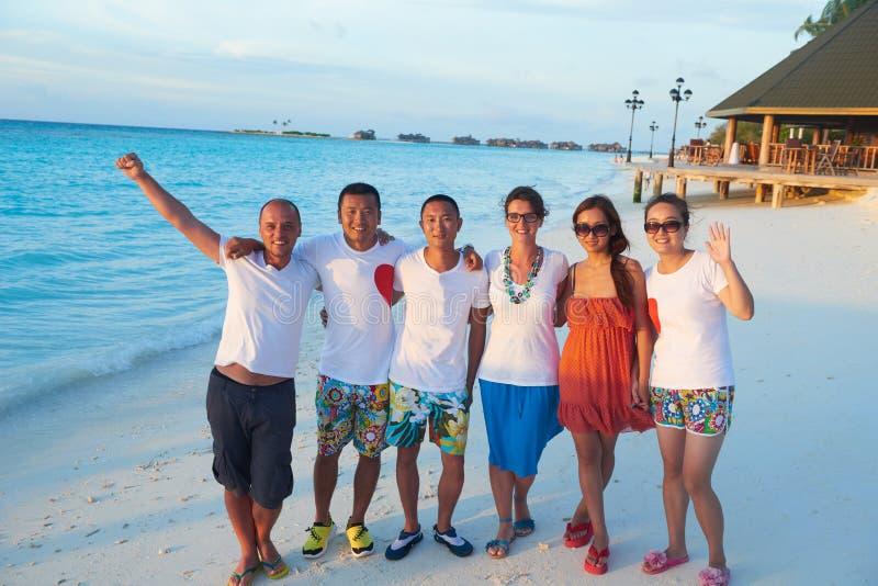 Gruppe Freunde auf schönem Strand stockbilder
