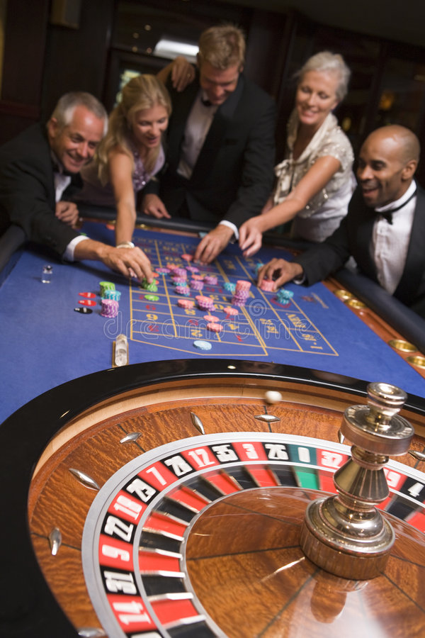 Gruppe Freunde des Spielens im Kasino lizenzfreie stockbilder