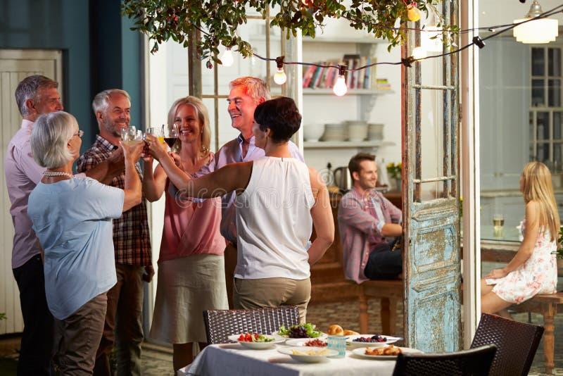 Gruppe Freunde, die Abend im Freien genießen, trinkt Partei stockfotografie