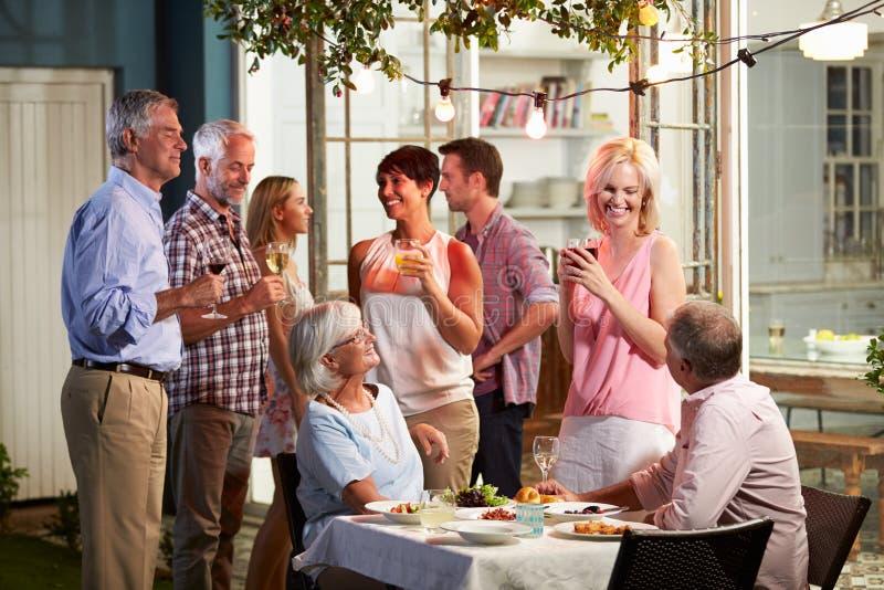 Gruppe Freunde, die Abend im Freien genießen, trinkt Partei lizenzfreie stockbilder