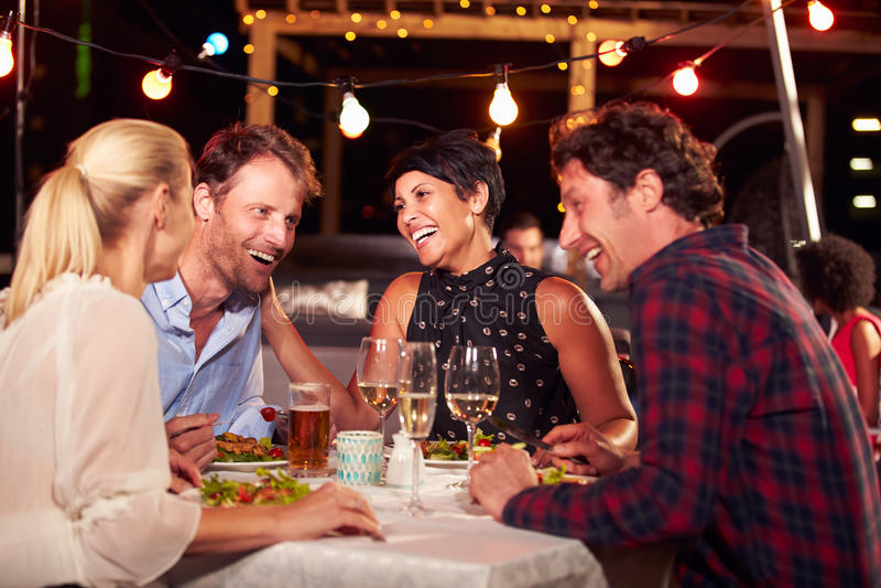 Gruppe Freunde, die Abendessen am Dachspitzenrestaurant essen lizenzfreies stockfoto