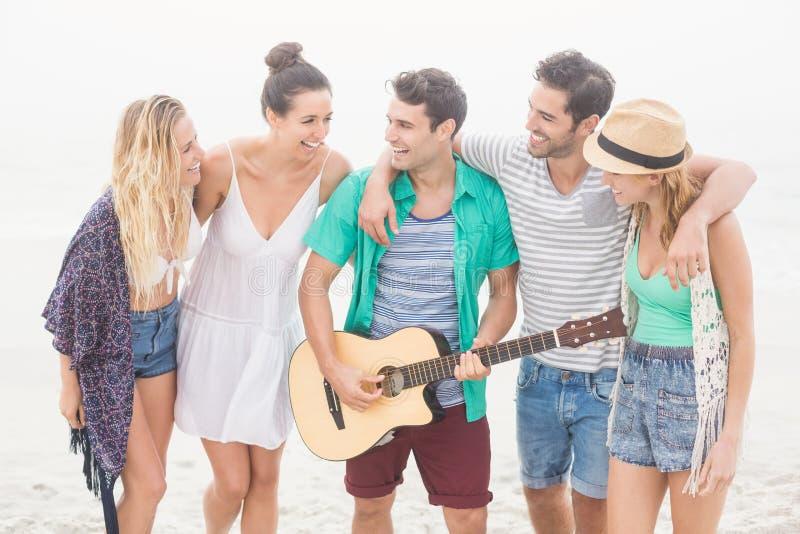 Gruppe Freunde, die auf dem Strand mit einer Gitarre stehen lizenzfreie stockbilder