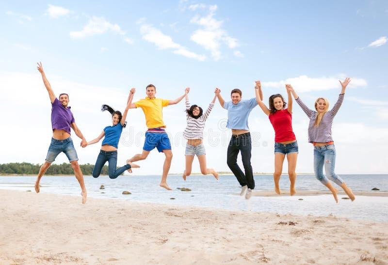 Gruppe Freunde, die auf den Strand springen stockfotografie