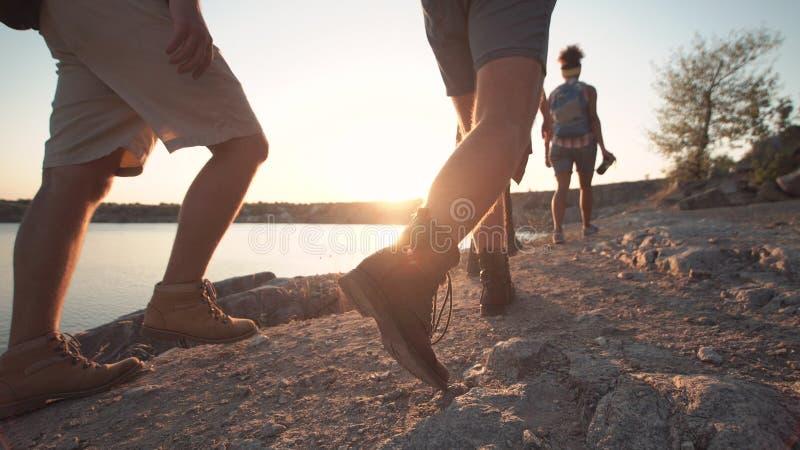 Gruppe Freunde, die auf felsiger Küstenlinie wandern lizenzfreies stockfoto