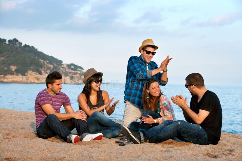 Gruppe Freunde, die auf Strand singen. lizenzfreies stockfoto