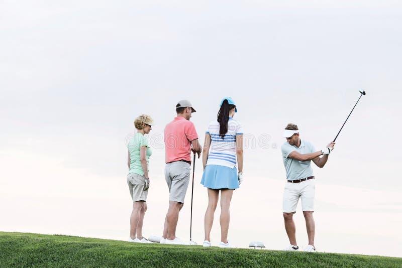 Gruppe Freunde, die den Mann spielt Golf gegen klaren Himmel betrachten stockfotos