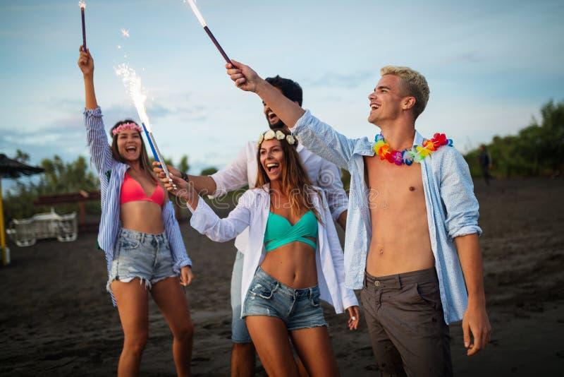 Gruppe Freunde, die den Spa? l?uft auf dem Strand mit Wunderkerzen haben lizenzfreies stockfoto