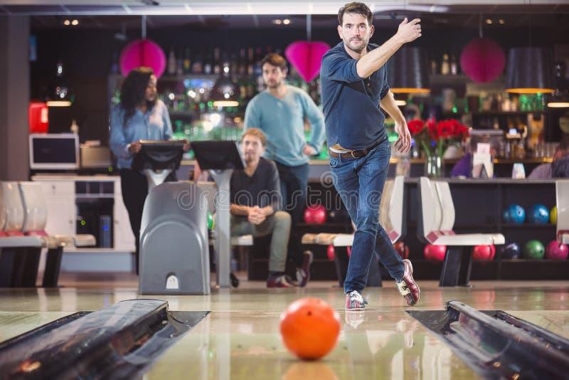 Gruppe Freunde, die in der Bowlingbahn spielen stockfotos