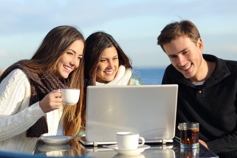 Gruppe Freunde, die einen Laptop in einem Restaurant aufpassen lizenzfreie stockfotos